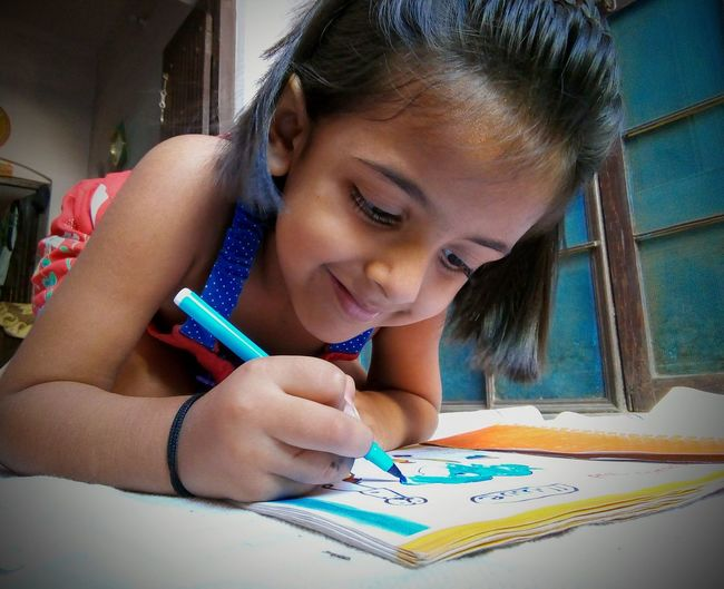 Happy Girl Making Drawing On Book