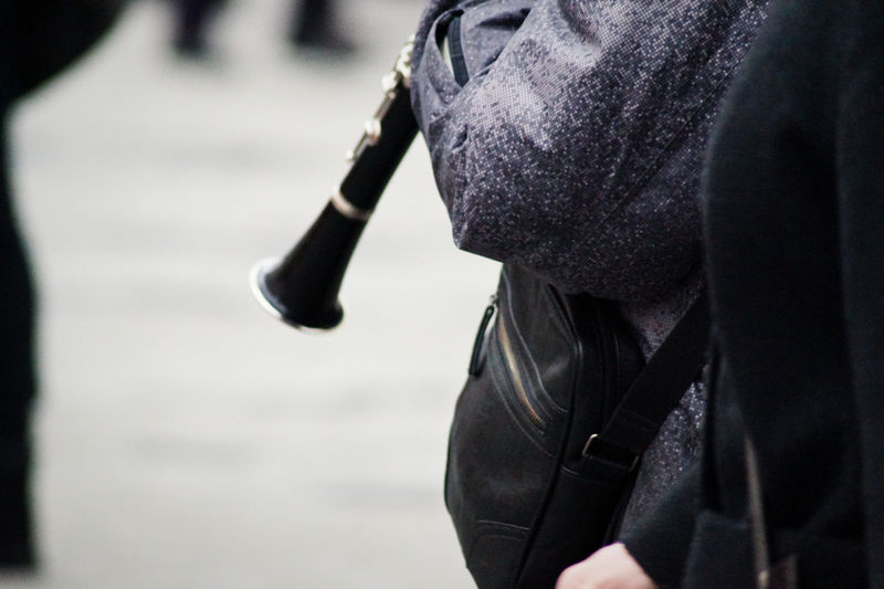 Close-up of person holding flute and standing on street
