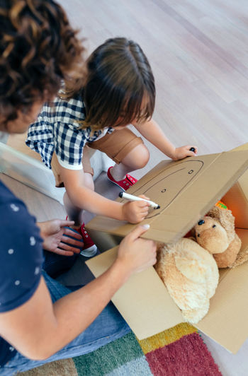 Little boy drawing in a moving box with his father Family Fun Happiness Happy Man Moving Unpacking Writing Boxes Boy Cardboard Home Interior House Indoors  Kid Lifestyles Living Room New Home Packing Painting Placing Real People Relocating Two People Vertical