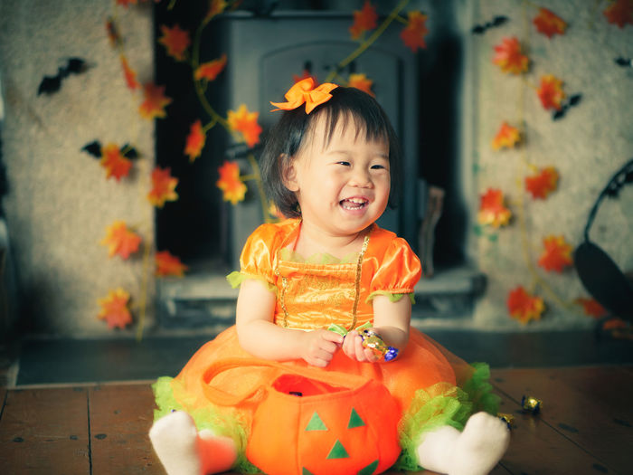 Cheerful baby girl sitting with jack o lantern basket at home
