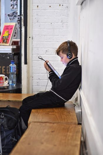 New generation with gadgets Snap a Stranger Wireless Technology One Person Side View Concentration Leisure Activity Music Rough Trade East Travel Photography Britain Brick Lane, London Sitting People Kids Mature Kids The Week Of Eyeem Fresh On Eyeem  Indoors  Technology Digital Music EyeEm LOST IN London