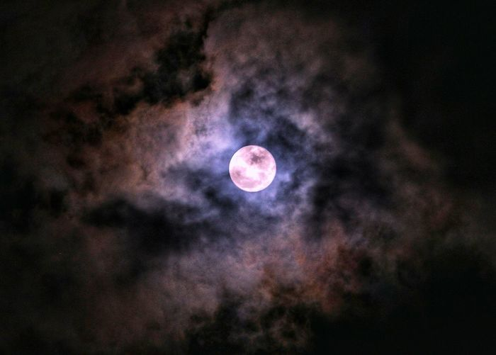 Low angle view of moon in dark sky