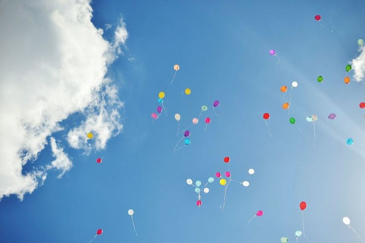 Low Angle View Of Balloons Flying Against Blue Sky