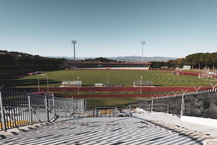 small stadium Outdoors No People Track And Field Built Structure Playing Field Absence Empty Practice Training Contest Match Poles Dribbling Field Goal Seats Play Football Competition Running Implant Track Grass Small Cement Architecture Pylons Light Bleachers Steps View Landscape Panorama Mountain Range Nature Movement Athletic Soccer Stadium Sport Grandstand