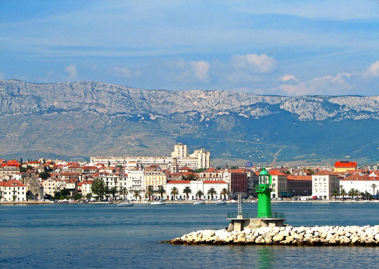 Croatian Coastal Town Mountain Range Background Architecture Beauty In Nature Building Exterior Built Structure City Cityscape Day Green Lighthouse House Mountain Mountain Range Nature No People Outdoors Residential Building Scenics Sea Sky Town Water Waterfront