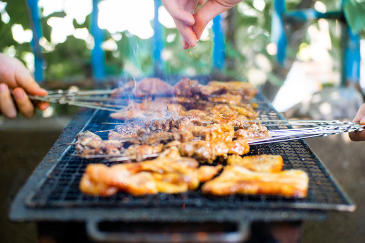 Cropped hands of people preparing food on barbecue grill