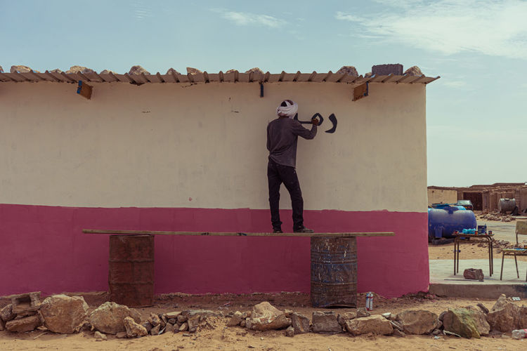 Rear view of man photographing against wall