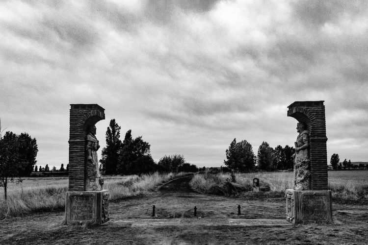 Statues On Field At Camino De Santiago Against Cloudy Sky