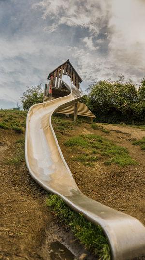 Slide at park against sky