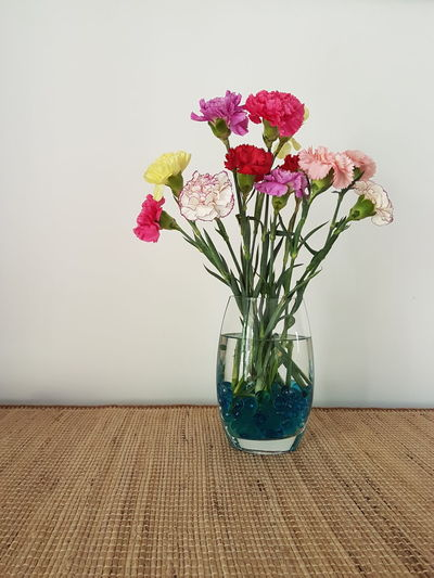 Flowers in vase on place mat against wall