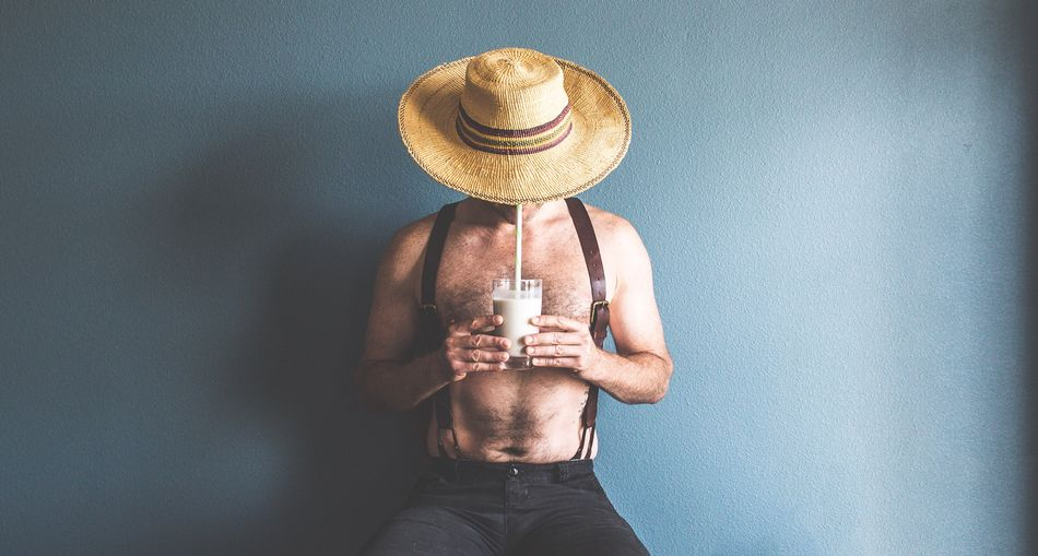 Shirtless Man Wearing Suspenders And Hat While Drinking Milk Against Wall
