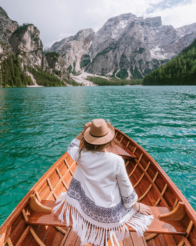 Rear view of woman wearing hat sitting in boat on lake