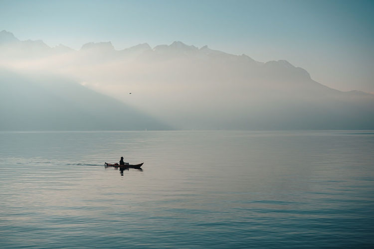 Beauty In Nature Fog Idyllic Mode Of Transportation Mountain Nature Nautical Vessel Outdoors Real People Reflection Rowing Scenics - Nature Sea Silhouette Sky Sun Tranquil Scene Tranquility Transportation Water Waterfront