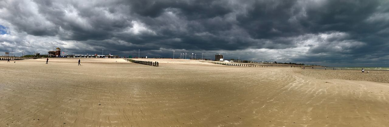 Panoramic view of beach against storm clouds