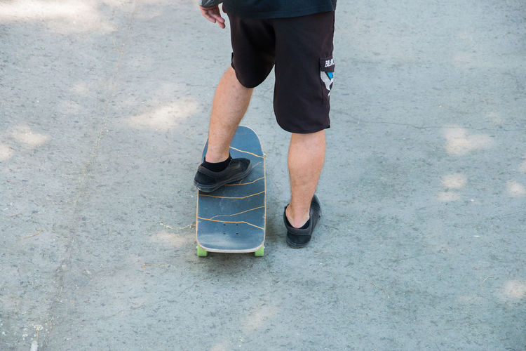 man skateboarding in a skatepark Low Section Human Leg Body Part Human Body Part Shoe One Person Standing Lifestyles Real People Sport Day Leisure Activity Men Footpath Casual Clothing Outdoors Human Limb Limb Sports Shoe Human Foot Shorts Jeans