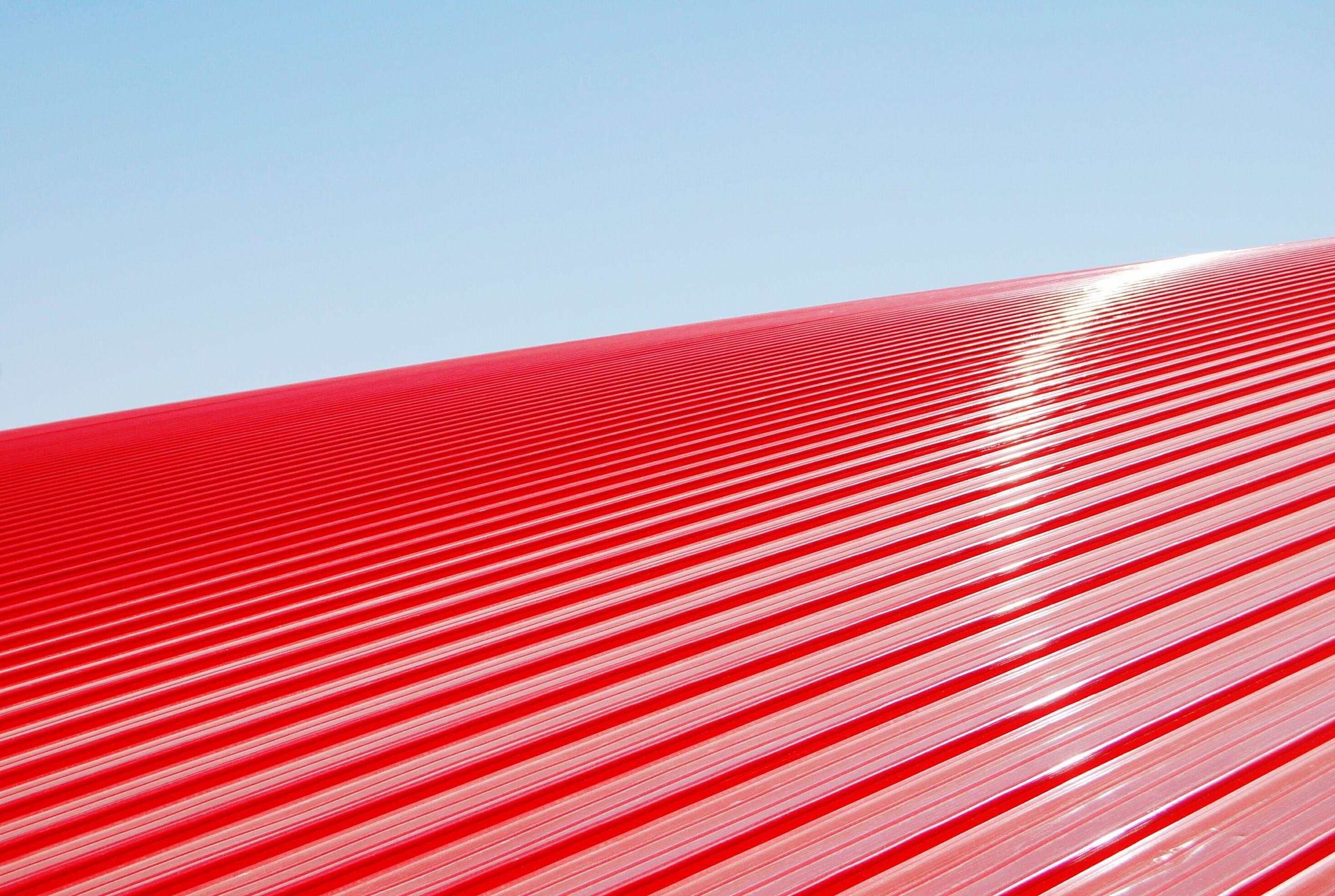 red, clear sky, built structure, architecture, pattern, copy space, low angle view, building exterior, striped, repetition, in a row, no people, roof, design, day, outdoors, blue, part of, sunlight, wall - building feature