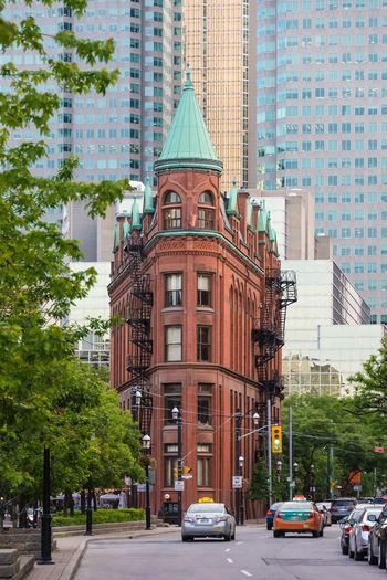 The red-brick Gooderham Building is a historic landmark. Completed in 1892, it was an early example of a prominent flatiron building. Architecture Building Building Exterior Built Structure Car City City Life City Street Incidental People Land Vehicle Mode Of Transport Office Building On The Move Road Street Tall - High Tower Traffic Transportation Tree