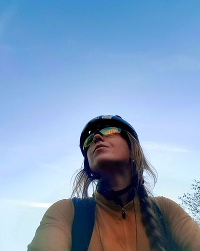 Low angle view of woman riding bicycle against blue sky