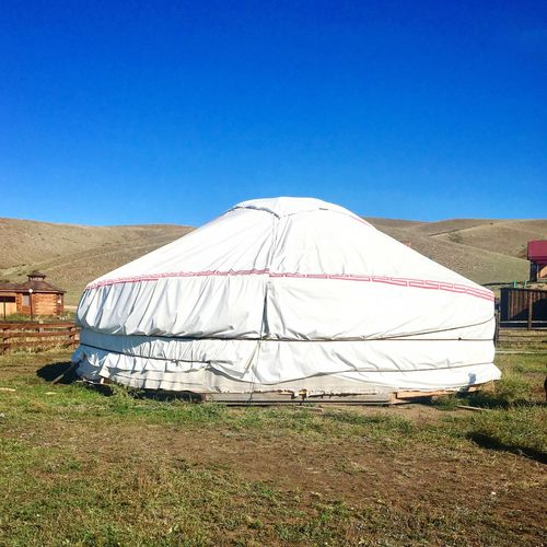 Tent on field against clear blue sky