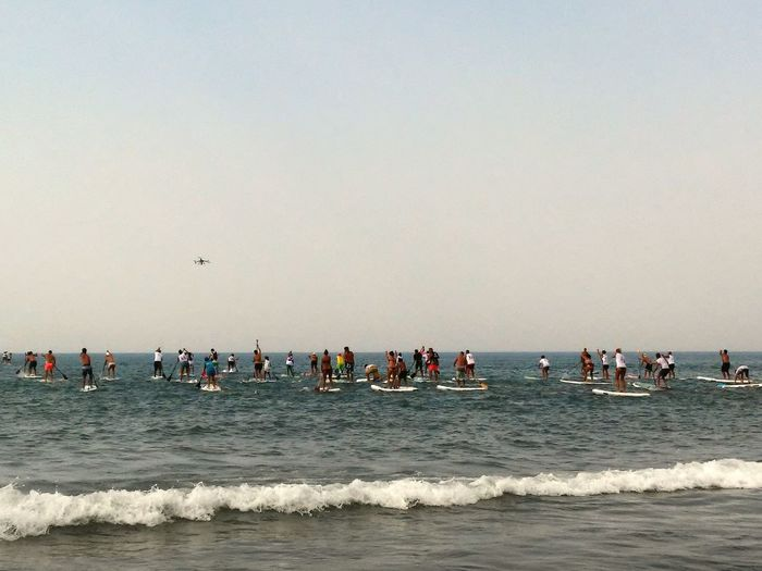 People participating in paddleboarding competition on sea