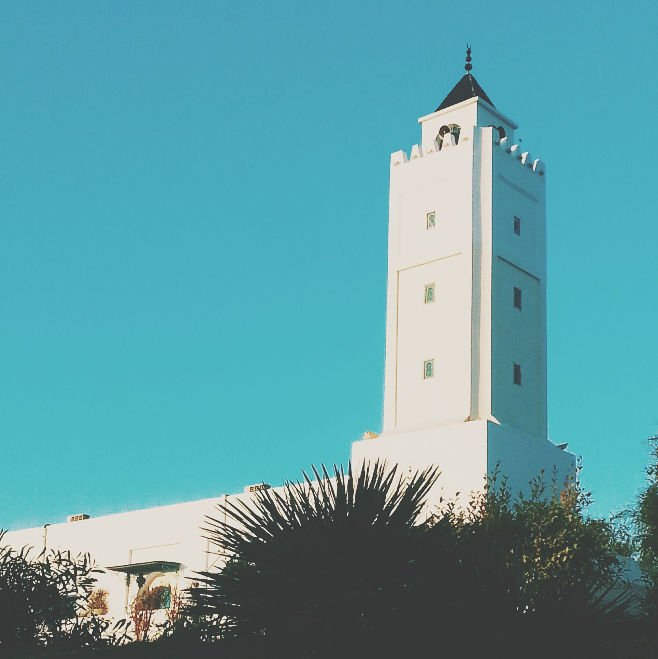 clear sky, blue, architecture, built structure, building exterior, copy space, low angle view, tower, religion, sunlight, church, place of worship, high section, no people, day, outdoors, tree, spirituality, building