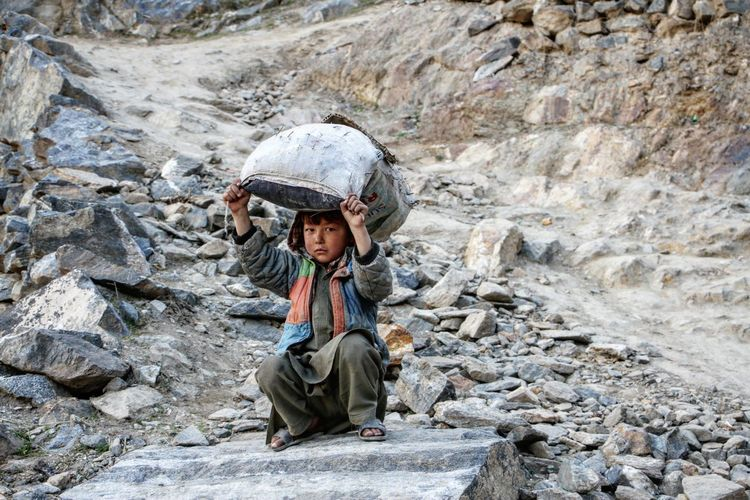 Portrait of boy sitting on rock