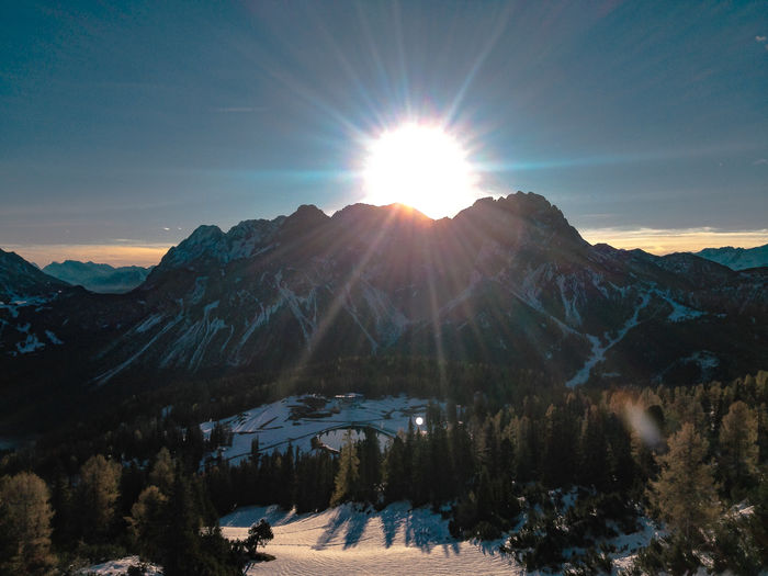 Scenic view of mountain against sun during winter