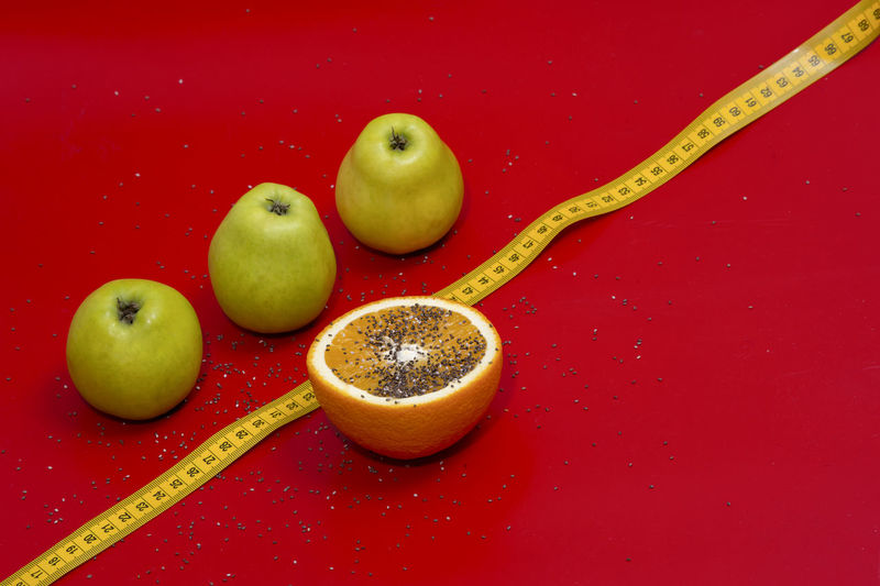 Close-up of fruits and tape measure over red background
