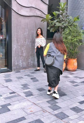Full length of women walking on footpath