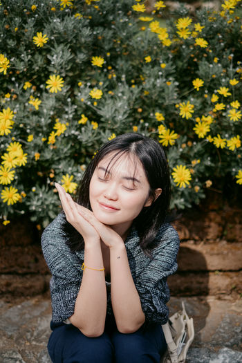 Portrait of a beautiful young woman sitting on yellow flower