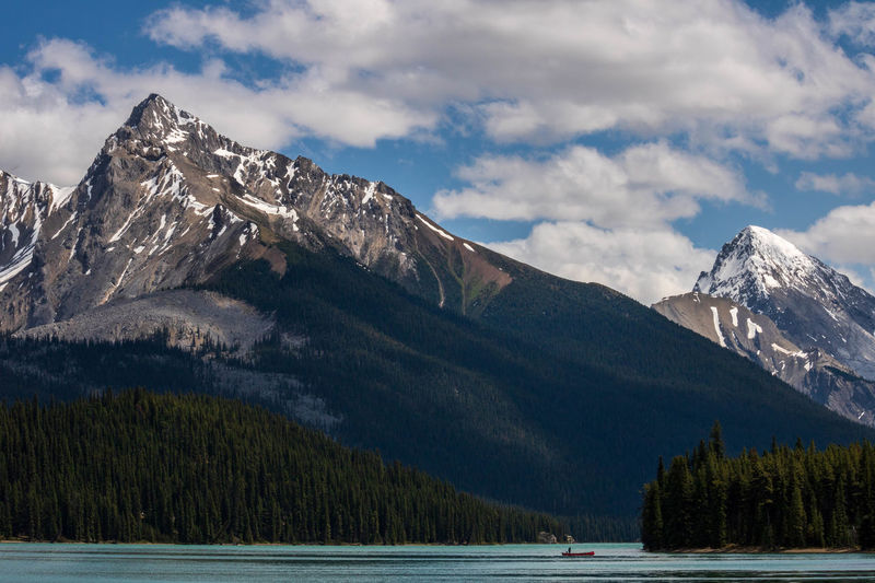 Kayaker on Maligne Lake Beauty In Nature Cloud - Sky Jasper National Park Kayak Lake Landscape Mountain Mountain Peak Mountain Range Nature Outdoors Peaceful Scenics - Nature Sky Snow Snowcapped Mountain Water
