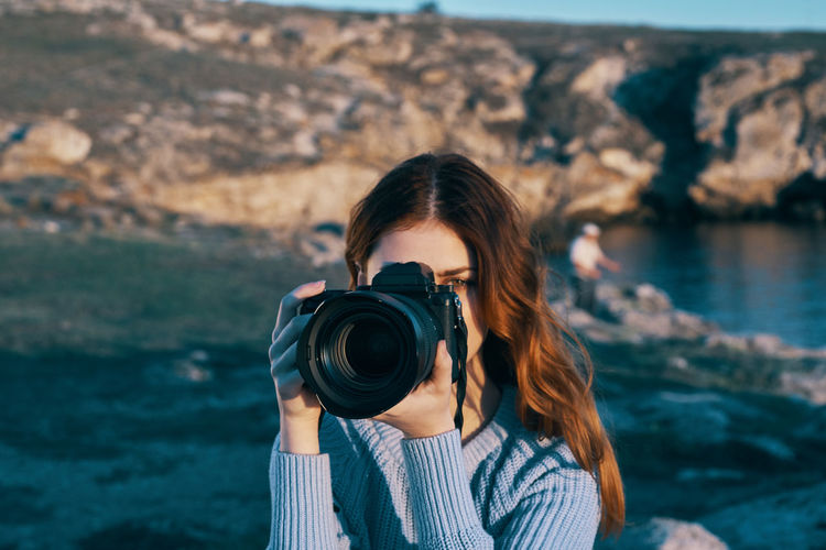Portrait of young woman photographing sea