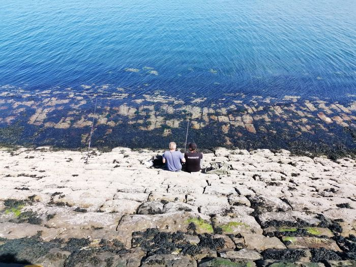 High angle view of people sitting on rock by sea