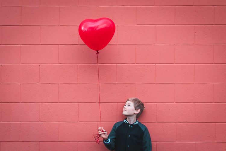 Boy Holding Balloon While Standing Against Brick Wall