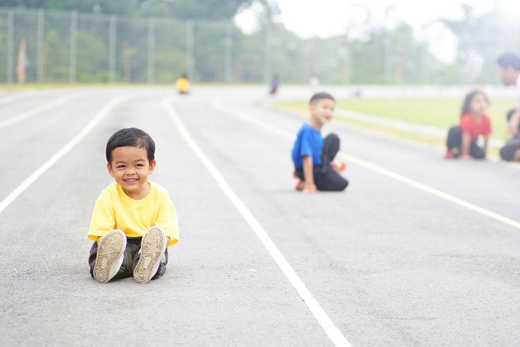 Portrait of smiling boy sitting on running track