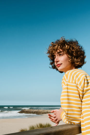 Beautiful young woman on beach against clear blue sky