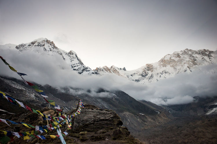 Prayer flags hanging over mountains against sky