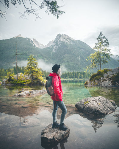Woman looking at lake against mountains