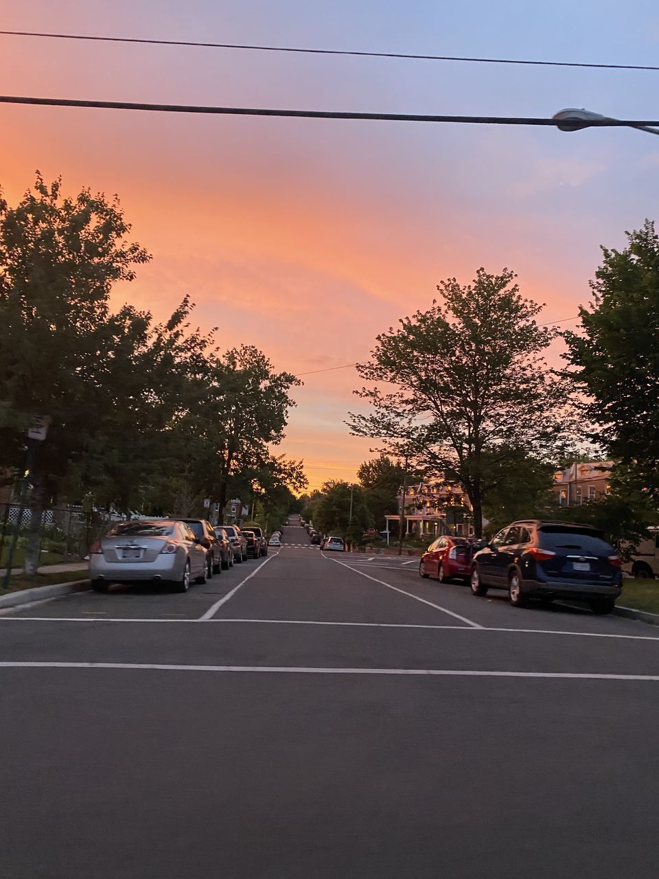 CAR ON STREET AGAINST SKY AT SUNSET