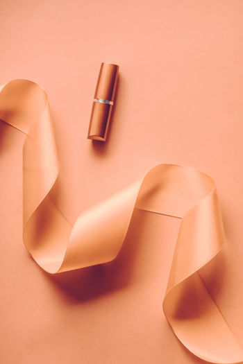 Close-up of lipstick on orange background