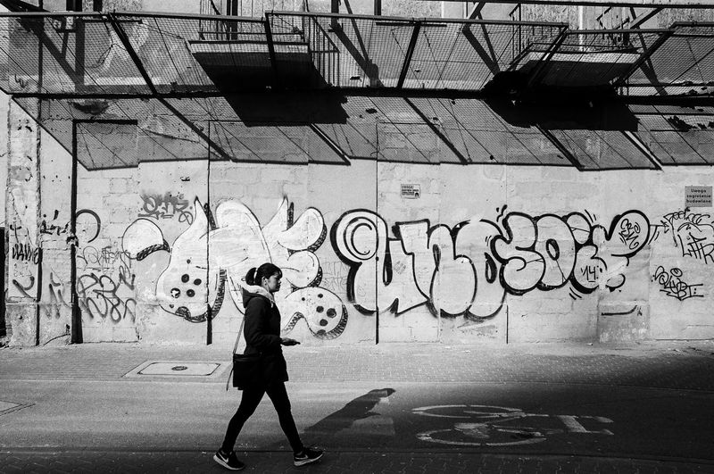 ANALOG; Rollei RPX 100 The Week on EyeEm Light And Shadow Capture The Moment Film Photography Rollei Analogue Photography Nikonphotography Street Photography Monochrome Black And White Bnw Spring Filmisnotdead Grain Graffiti One Person Real People Wall - Building Feature Lifestyles Architecture Full Length Creativity Women Built Structure Leisure Activity Day Art And Craft Casual Clothing Standing Street Art City Building Exterior Side View Outdoors