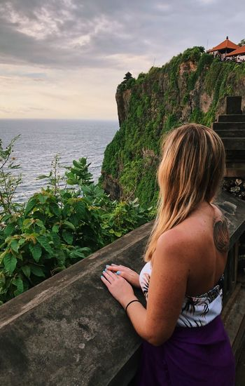 High angle view of woman looking at sea while standing by retaining wall during sunset