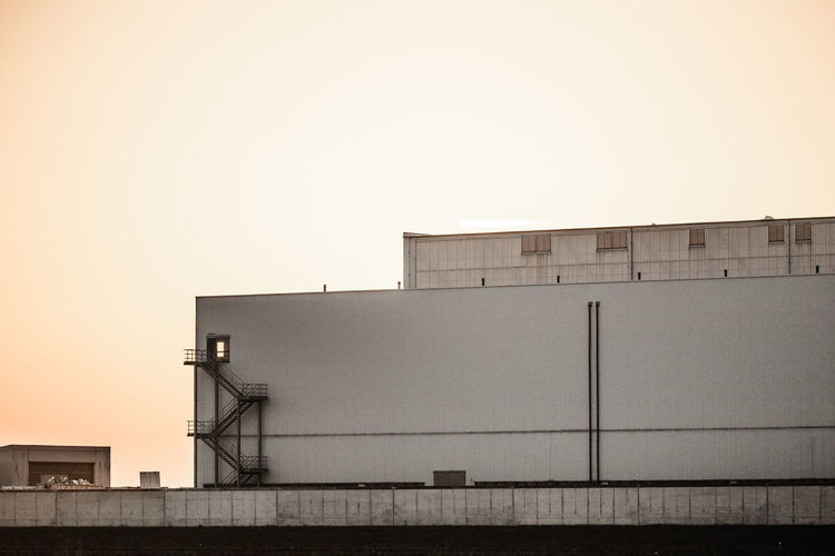 Low Angle View Of Factory Against Sky At Sunset