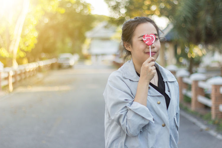 Portrait of young woman with lollipop
