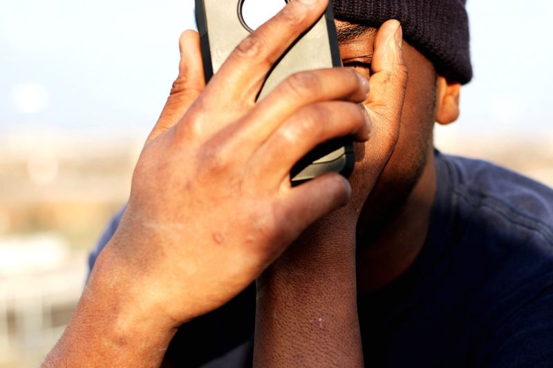 Man covering face with mobile phone in sunlight