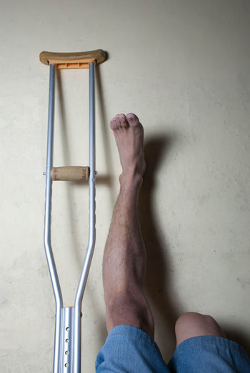 Low section of man leaning by crutch on wall