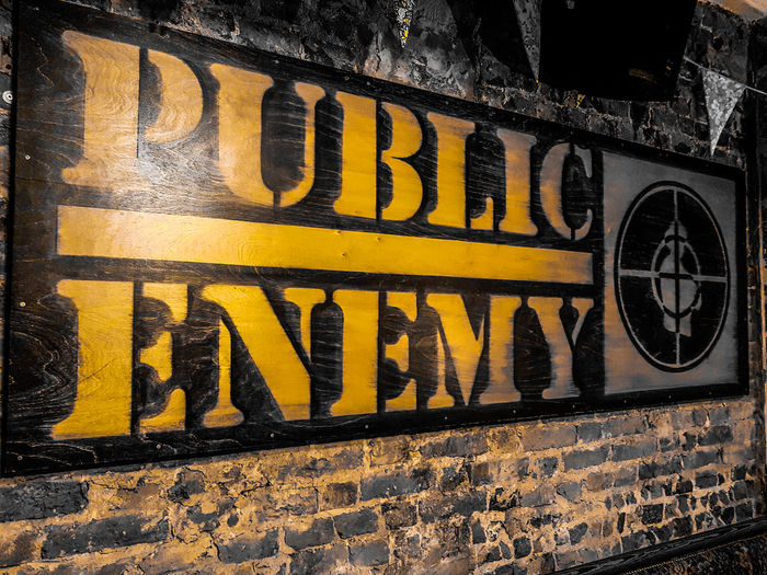 Pub life. Yellow Text Black Color Communication Textured  No People Close-up EyeEm Gallery Fresh On Eyeem  Ayeshea Bah Light Brick Wall Textured  Backgrounds Hanging Atmospheric Scene Music Band Public Enemy Rappers Lyrics Political Statement Pub Life Decoration Poster