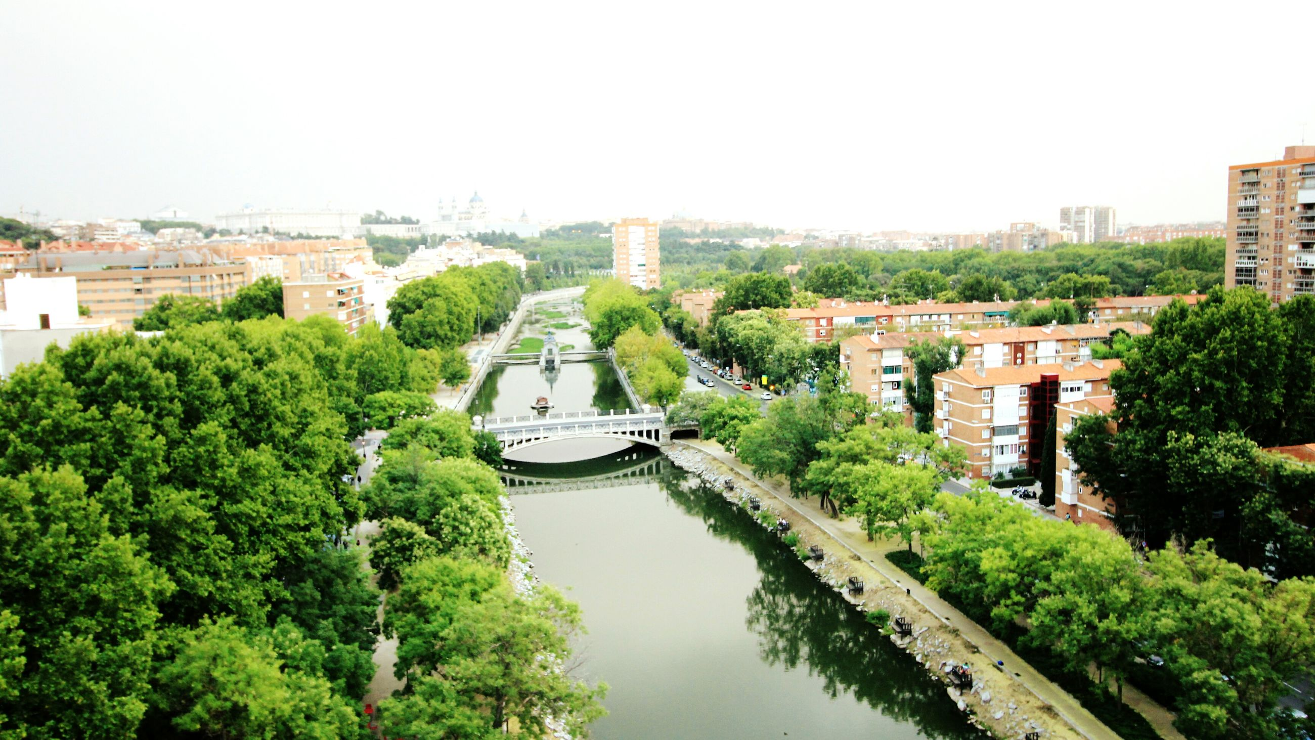 architecture, building exterior, built structure, tree, water, canal, transportation, high angle view, city, clear sky, mode of transport, residential building, nautical vessel, waterfront, residential structure, river, house, residential district, boat, incidental people