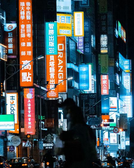 Information sign on illuminated street in city at night
