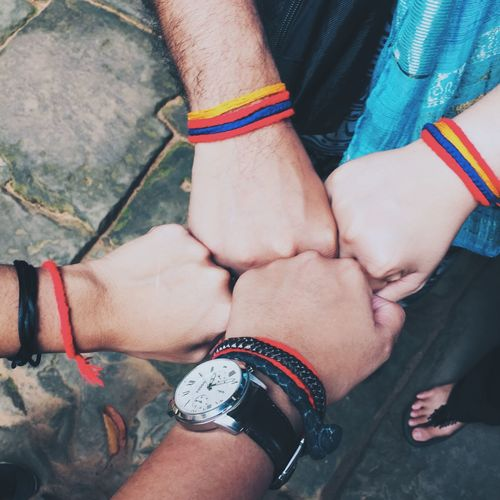 Cropped image of friends wearing bracelets